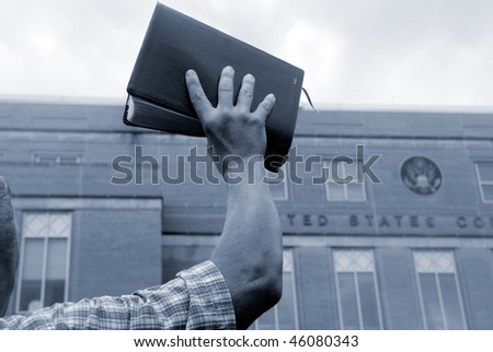 Man holding up bible in front of court house - stock photo