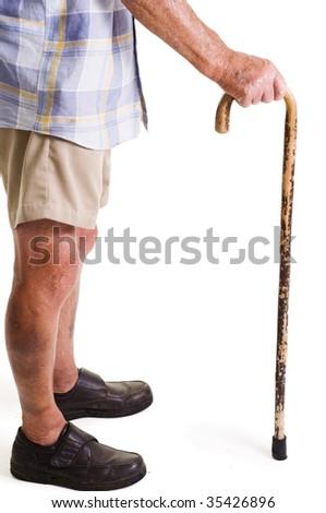 Man holding walking stick while wearing summer clothing - stock photo