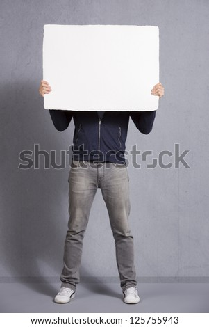 Man holding white empty signboard with space for text in front of his face, isolated on grey background. - stock photo