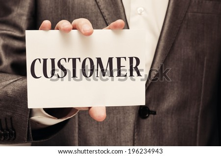 Man holding white paper with word Customer written on it - stock photo