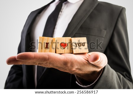 Man holding wooden blocks with I love you message and a hand-drawn red heart balanced in the palm of his hand in an anniversary or Valentines Day concept. - stock photo