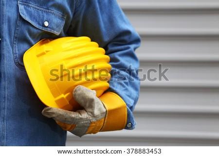 Man holding yellow helmet close up, shallow dof - stock photo