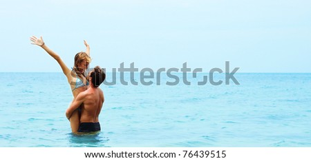 Man holding young woman in the hands in the blue sea - stock photo