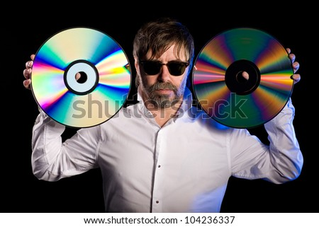 Man holds a retro laser discs on a black background. - stock photo