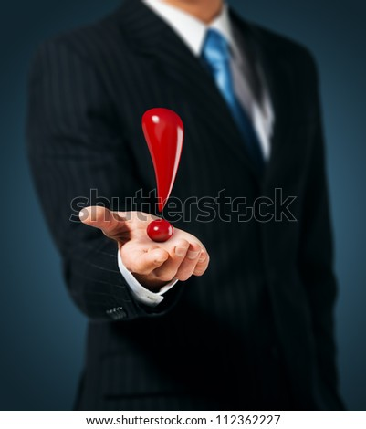 Man holds an exclamation mark in a hand - stock photo