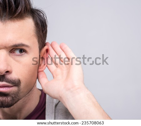 Man holds his hand to his ear.  He secretly eavesdropping on a private conversation. The human face, expression, emotion, body language. - stock photo