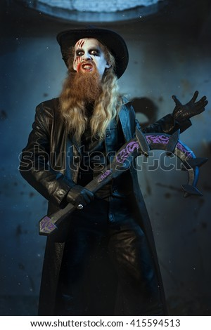 Man holds in his hand a sickle, he is an evil and terrible. - stock photo