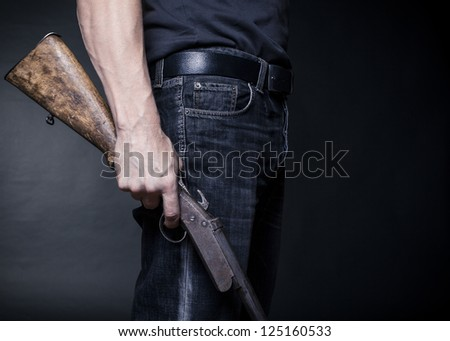 man holds in his hand an old shotgun.Black background - stock photo