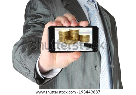 Man holds smart phone with business composition of graphs and money on white background - stock photo