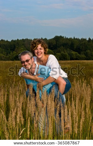 man holds  woman on hands on a meadow - stock photo