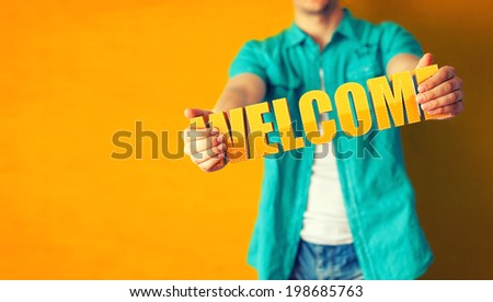 Man holds word welcome on bright colorful background - stock photo
