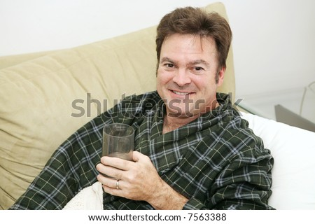 Man home sick from work drinking lots of fluids to get better. - stock photo