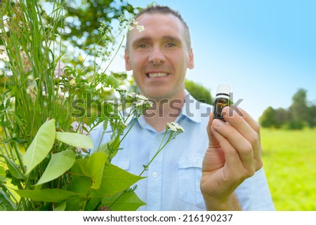 Man homeopath herbalist picking up wild herbs with a bottle in hand - stock photo