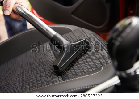 Man Hoovering Seat Of Car During Car Cleaning - stock photo