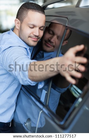 Man hugging a car in a car dealership - stock photo