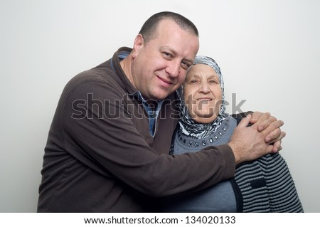 Man hugging his Mother wearing Hijab - stock photo