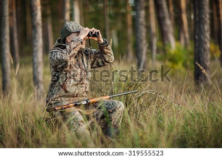 man hunter with shotgun looking through binoculars in forest - stock photo