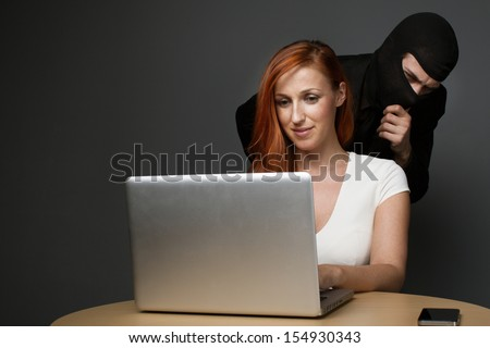 Man in a balaclava furtively watching an unsuspecting female office worker working on her laptop computer while corporate spying, stealing personal or business information or employee monitoring - stock photo