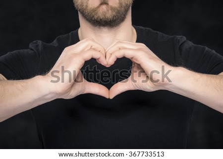 Man in a black shirt showing hand gesture heart on dark background. - stock photo