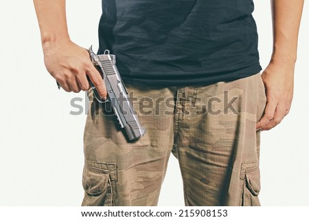 Man in a camouflage pants holding a gun, Army, Semi-automatic handgun, 45 pistol. (Color Process) - stock photo