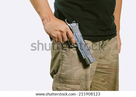 Man in a camouflage pants holding a gun, Semi-automatic handgun, Army, 45 pistol. (Color Process) - stock photo