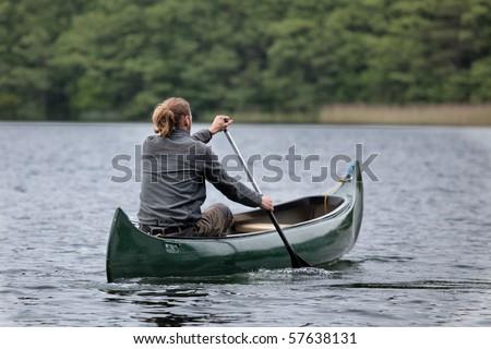 Man in a canoe - stock photo