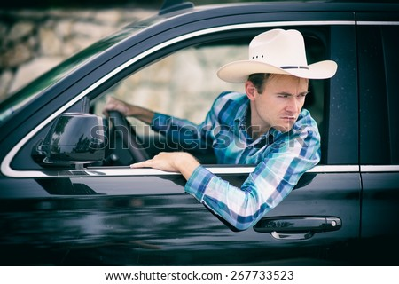 Man in a car driving backwards - stock photo