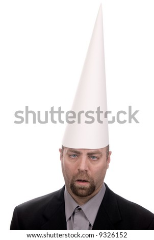 Man in a dunce cap with eyes crossed over a white background - stock photo