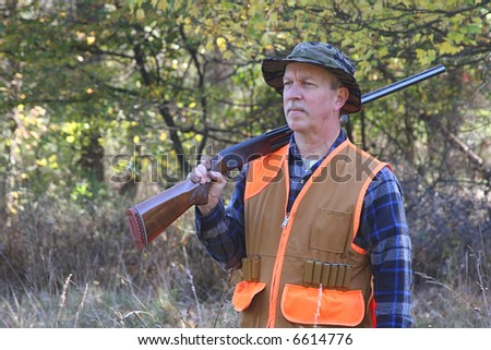 Man in a field hunting and carrying a shotgun - stock photo
