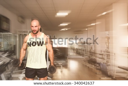 Man in a fit shape working out his biceps and arms using dumbbells in a gym with a powerful movement energetic soft filter effect applied suggesting bodybuilding - stock photo