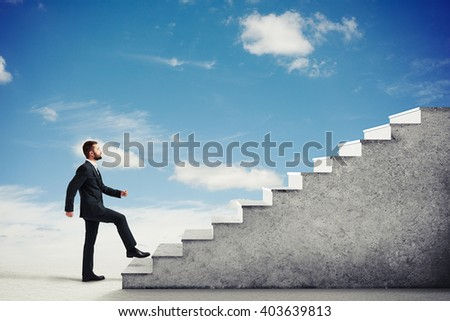 Man in a formal wear climbing concrete stairs in a light cloudy sky, side view - stock photo