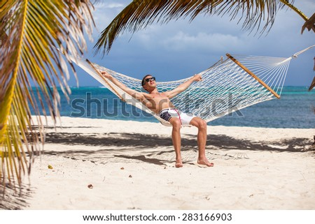 Man in a hammock on the beach. - stock photo