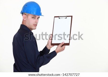 Man in a hardhat with a blank clipboard - stock photo