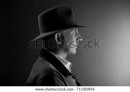 Man in a hat looking at the light - stock photo