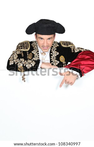 Man in a matador costume with a board blank for text or image - stock photo