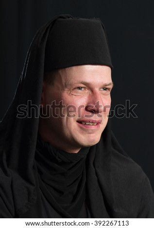Man in a monk robe on a black background. - stock photo
