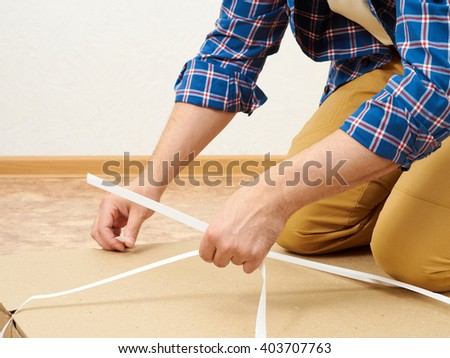 Man in a plaid shirt opens the box with furniture.   - stock photo