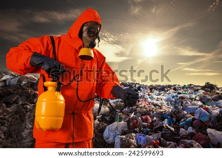 Man in a protective workwear working on the landfill - stock photo