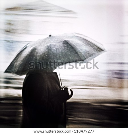 Man in a rain walking with umbrella. Unrecognizable person in motion blur. - stock photo