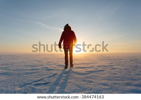 man in a red jacket in the snow with vintage camera - stock photo