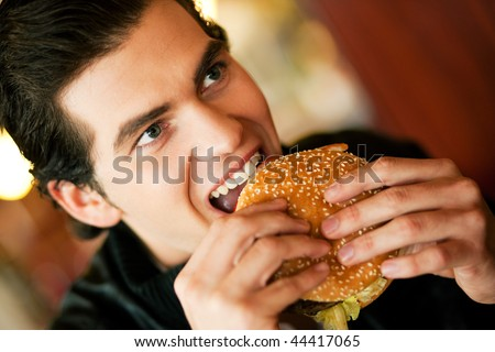 Man in a restaurant or diner eating a hamburger, he is hungry and having a good bite, shot with available light, very selective focus - stock photo