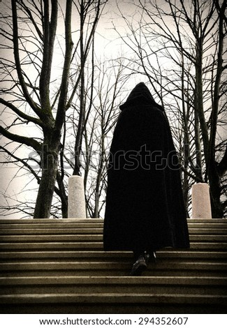 man in a robe climbing stairs - stock photo