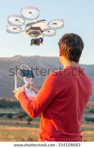Man in a rural environment guiding a drone  - stock photo