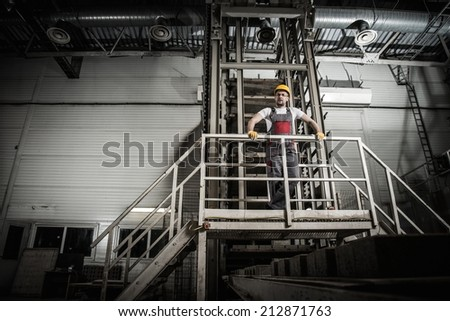 Man in a safety hat on a factory   - stock photo