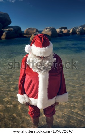 Man in a Santa Claus costume with his bare feet in the calm water of a beach - stock photo