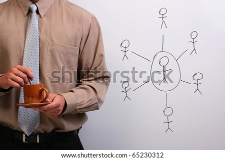 Man in a shirt and a tie holding a plate and a cup next to a drawing of a hierarchy. - stock photo