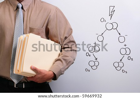 Man in a shirt and a tie holding manila folders while standing next to a drawing of ozone formation. - stock photo