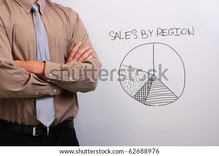 Man in a shirt and a tie standing next to a whiteboard with a drawing of a pie chart. - stock photo