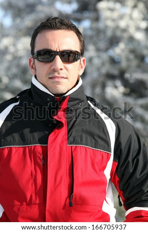 Man in a ski jacket and sunglasses - stock photo