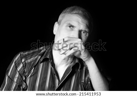 Man in a striped shirt at the age of forty-six years old smoking and looking at the camera on the black background - stock photo